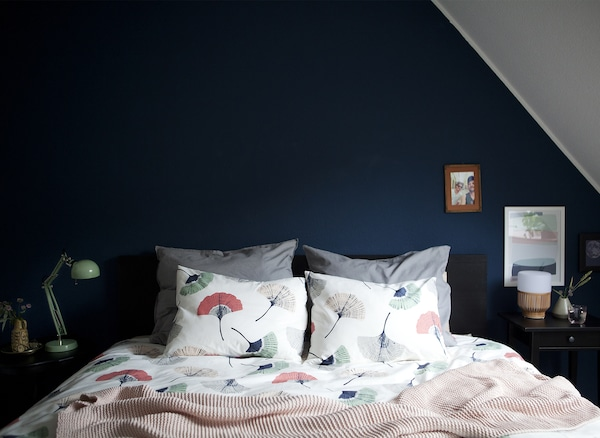 A dark blue bedroom wall and coordinating bed covers.