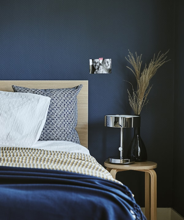 A dark blue bedroom with a bed and bedside stool.