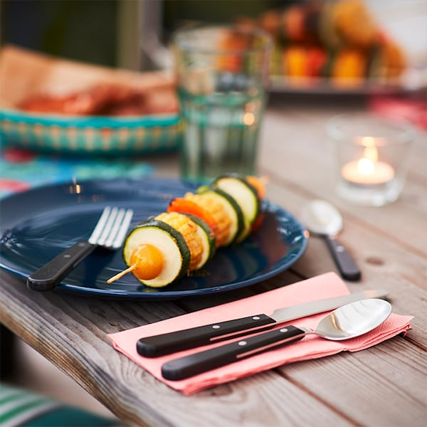 A dark blue dinner plate with a light pink napkin folded to the right that has cutlery resting on top. The dinner plate has a vegetable kabob on it and there is a lit candle and drinking glass in the background.