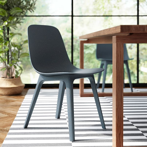 A dark blue ODGER chair made from recycled plastic, placed on a striped grey and white rug.