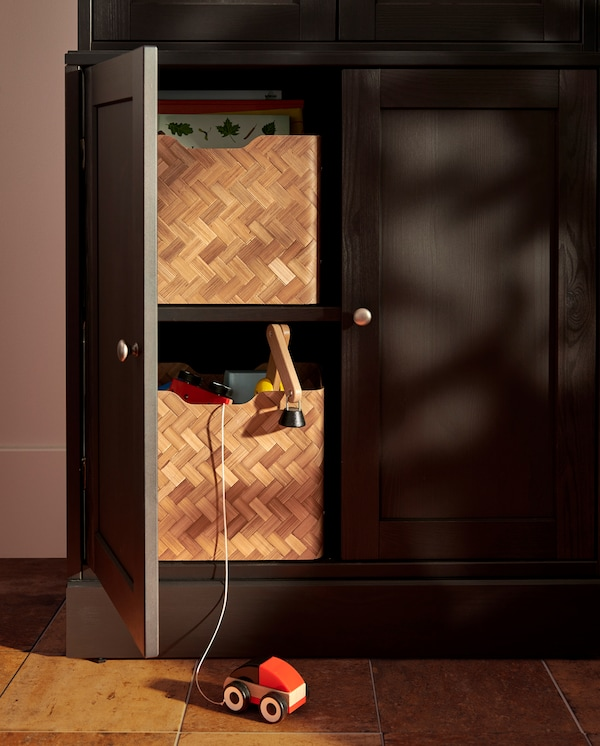 A dark brown base cabinet has one door open, inside are two shelves with two bamboo boxes with books and children's toys.