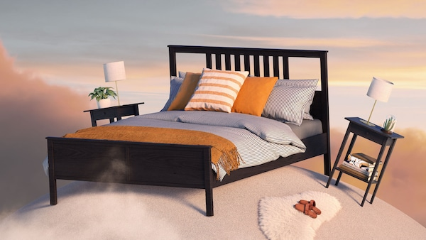 A dark brown HEMNES bed with two matching nightstands with table lamps, placed on a small carpeted planet, floating in the sky at sunset.