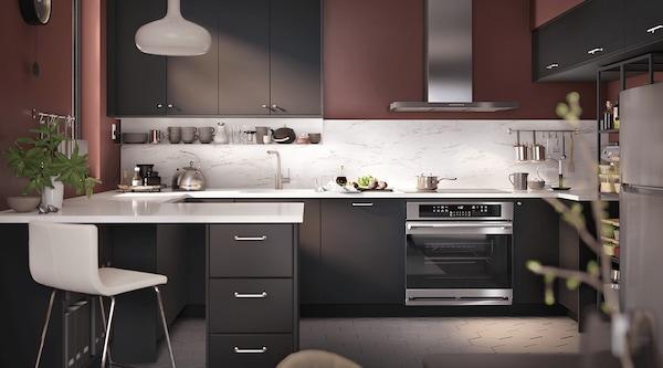 A dark brown kitchen featuring stainless steel appliances.