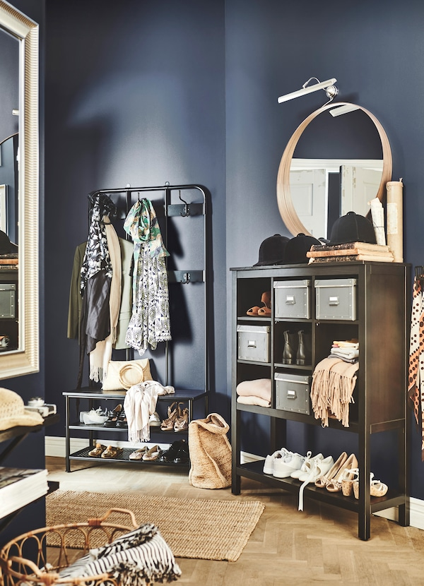 A dark brown shoe cabinet and a clothes hanging unit in a room with a dark blue painted wall.