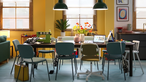 A dark-brown STRANDTORP extendable table surrounded by multiple chairs and arranged for various everyday activities.