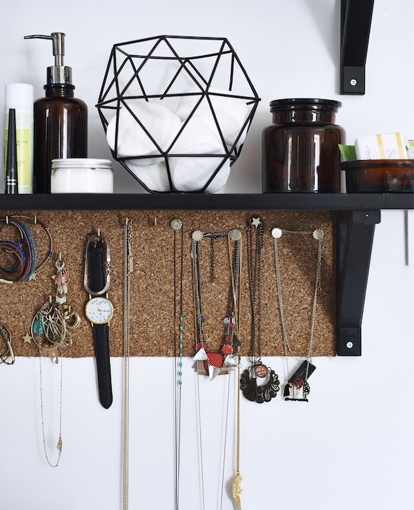 A dark brown, wall-mounted shelf and cork board filled with storage jars and jewellery.