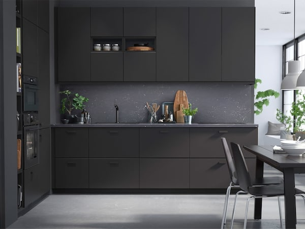 A dark colored kitchen with black cabinet fronts and a gray backsplash.