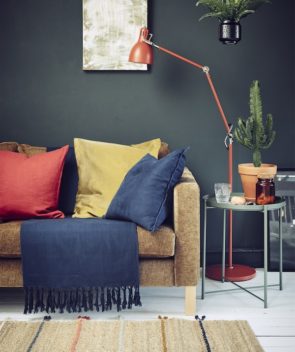 A dark-colored living room with a sofa, lighting and bold textiles.