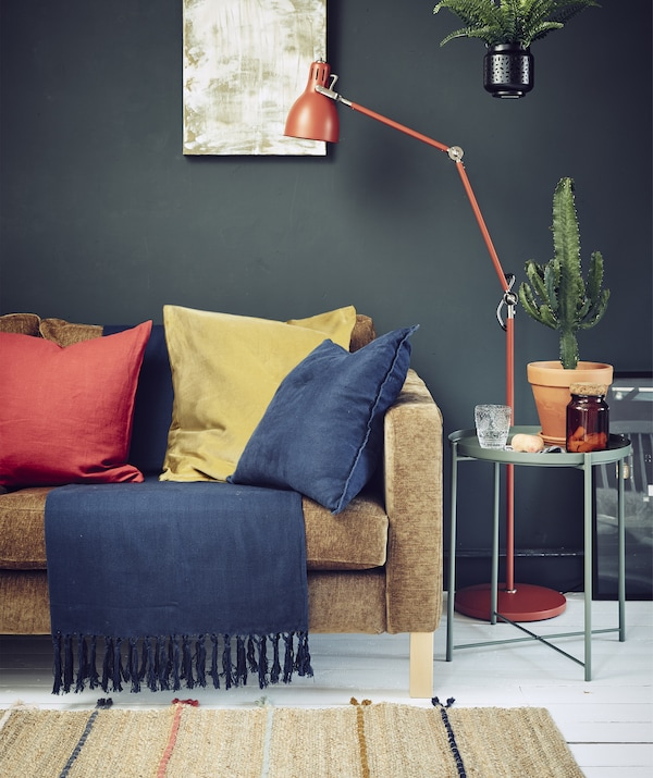 A dark-coloured living room with a sofa, lighting and bold textiles.