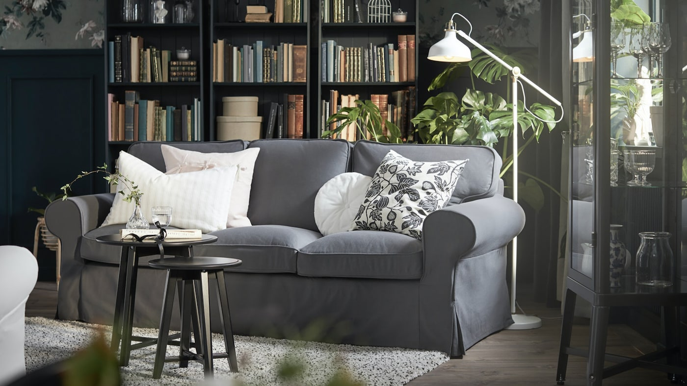 A dark gray sofa with a standing lamp and plants behind it, bookshelves, and a display cabinet in a gray living room.