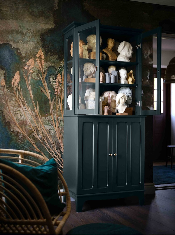 A dark green cabinet with glass doors is full of old-fashioned sculptures.