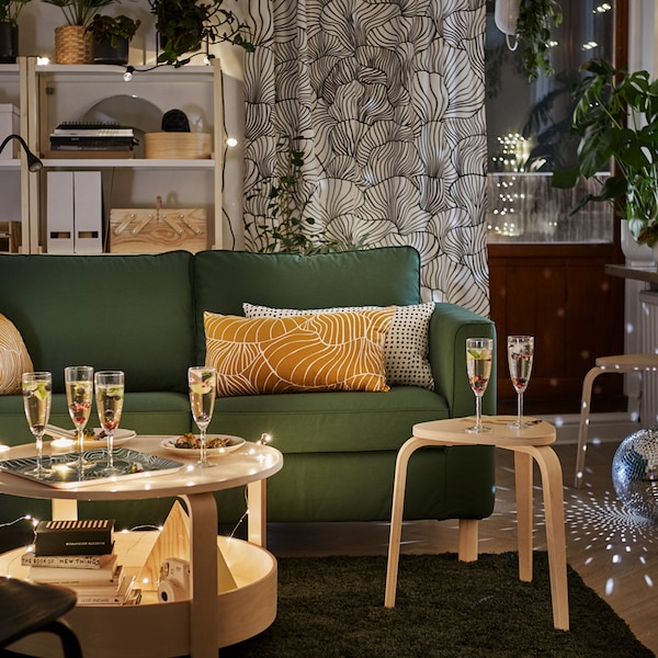 A dark green PÄRUP two-seater sofa with cushions is in a living room with a coffee table with champagne flutes.