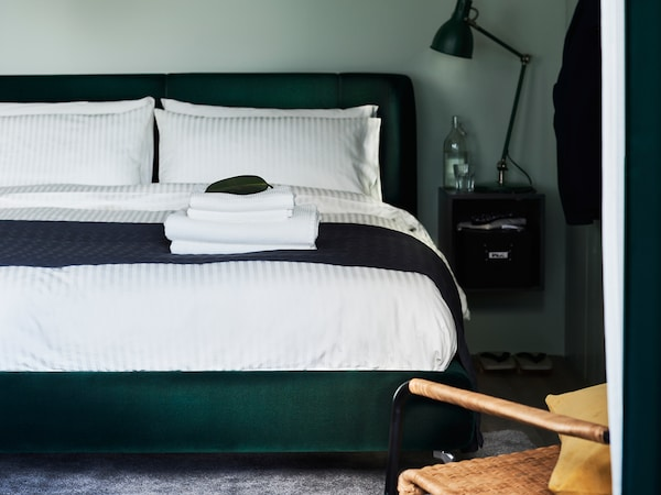 A dark-green TUFJORD upholstered bed with NATTJASMIN bed linen stands in a bedroom against a green wall.