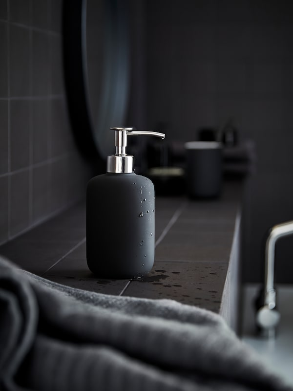 A dark grey bathroom with an EKOLN soap dispenser and a grey towel on a shelf, a black framed mirror in the background.