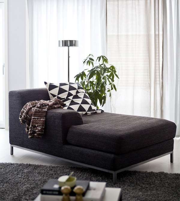 A dark grey chaise longue in a monochrome living space.