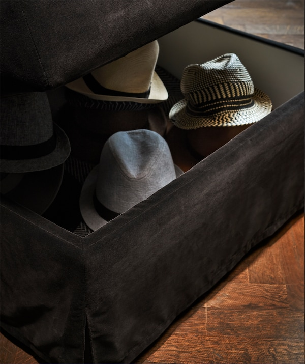A dark grey FÄRLÖV footstool with storage with hats inside.