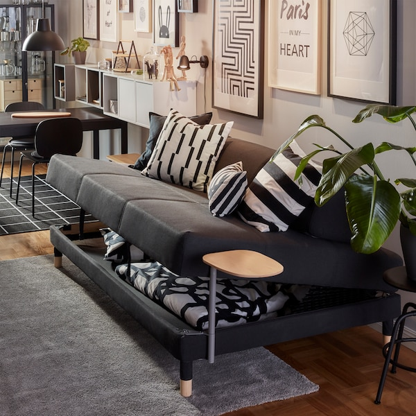 A dark grey FLOTTEBO sofa-bed where the seat has been lifted, underneath it is storage space with a duvet and a pillow.