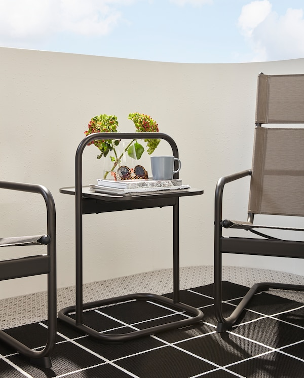 A dark grey HUSARÖ side table with handle stands on a rug between two armchairs. Sunglasses and a mug stand on the tabletop.