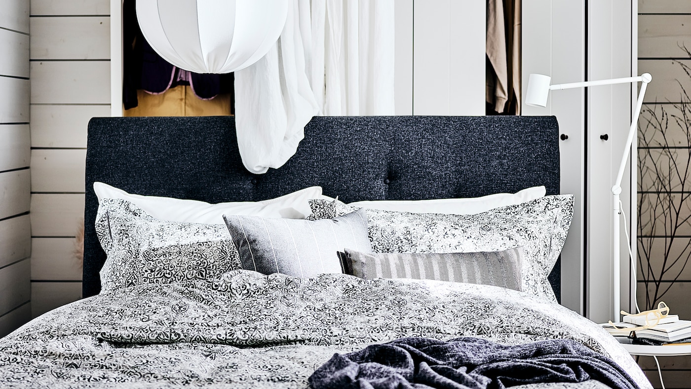 A dark grey IDANÄS upholstered bed with a white curtain and a white wardrobe behind it and a white pendant lamp above it.