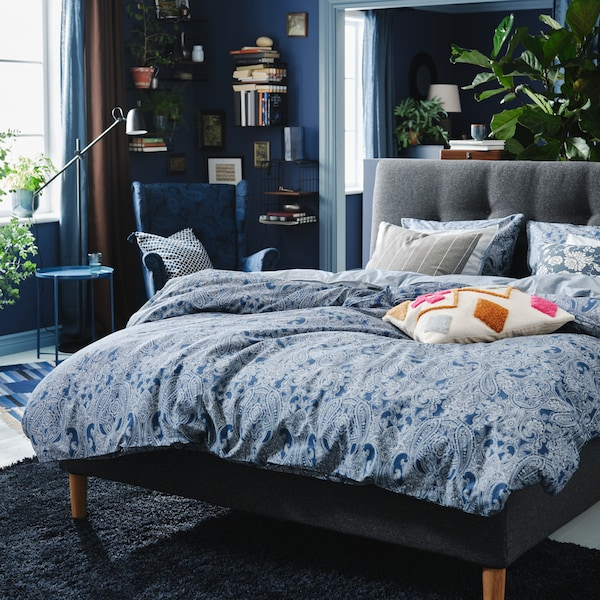 A dark grey IDANÄS upholstered bed with JÄTTEVALLMO bed linen stands in a bedroom with a dark blue VOLLERSLEV rug.