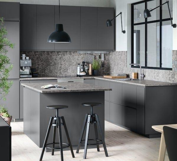 A dark grey IKEA kitchen with bar stools.