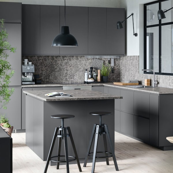 A dark grey IKEA VOXTORP kitchen with island and stools.
