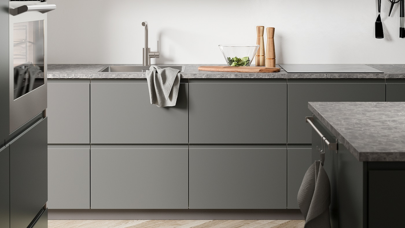 A dark-grey kitchen with VOXTORP dark-grey kitchen fronts, a dark-grey stone-effect worktop, and an island.