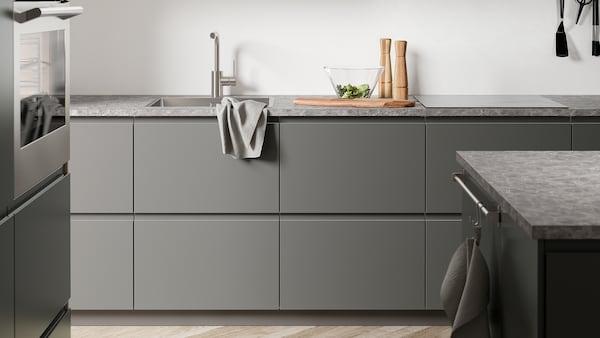 A dark-grey kitchen with VOXTORP dark-grey kitchen fronts, a dark-grey stone-effect worktop, and an island.