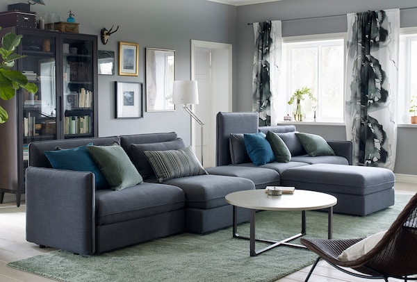 A dark grey, modular sofa with green and blue accessories.