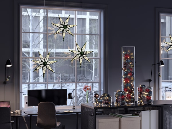 A dark grey office space with holiday themed decor such as illuminated stars hanging in the window and cylinders filled with Christmas balls.