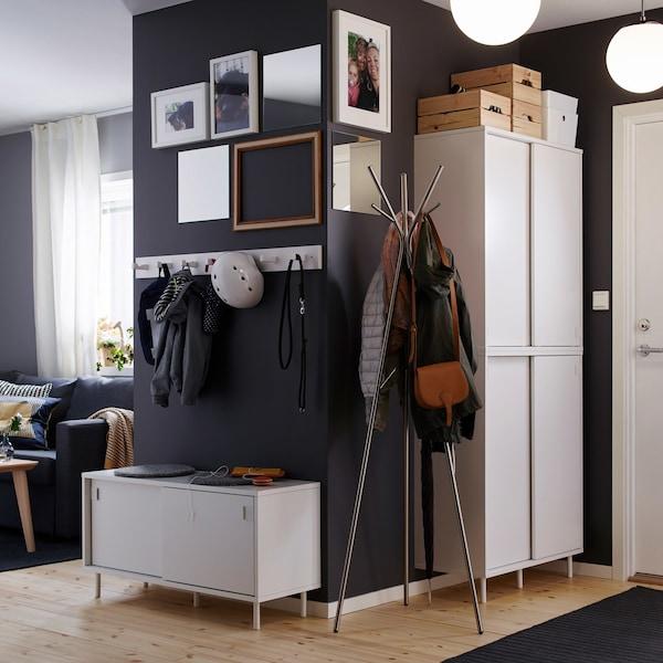 A dark grey open hallway with white storage units and coat hooks.
