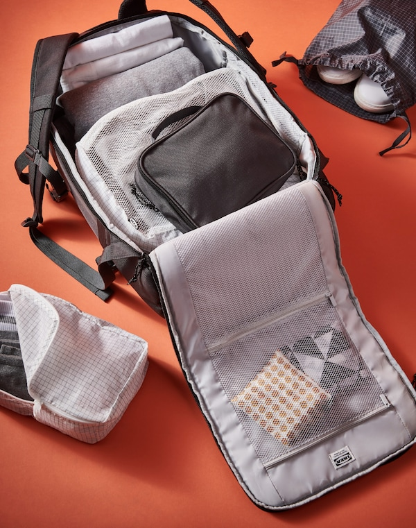 A dark grey VÄRLDENS backpack unzipped and filled with RENSARE bags on an orange surface.