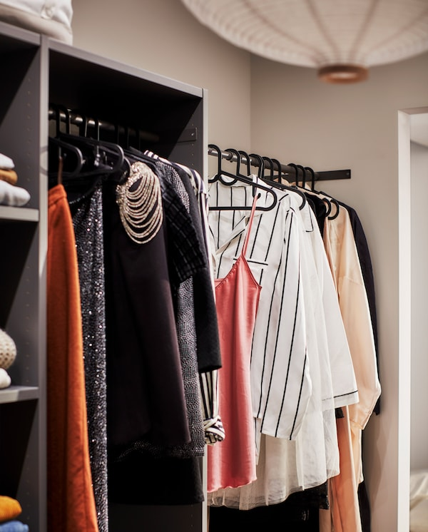 A dark grey wardrobe with black rods where many clothes hang on thin black clothes hangers.