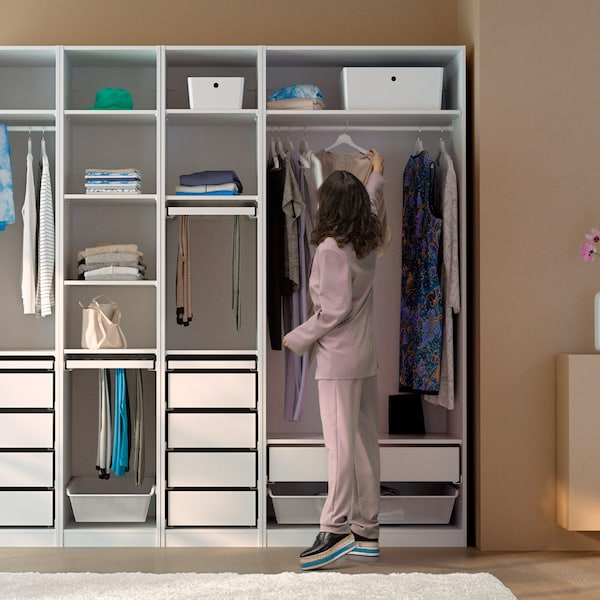 A dark-haired woman in a pink trouser suit hangs a dress on the clothes rail of a white, open PAX wardrobe combination.
