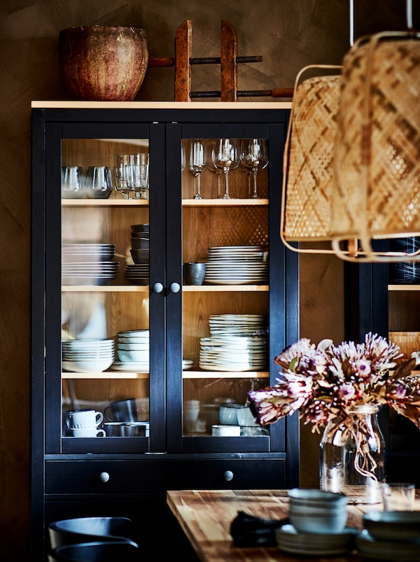 A dark HEMNES glass-door cabinet filled with stacks of tableware, standing by a wall next to a dining table.