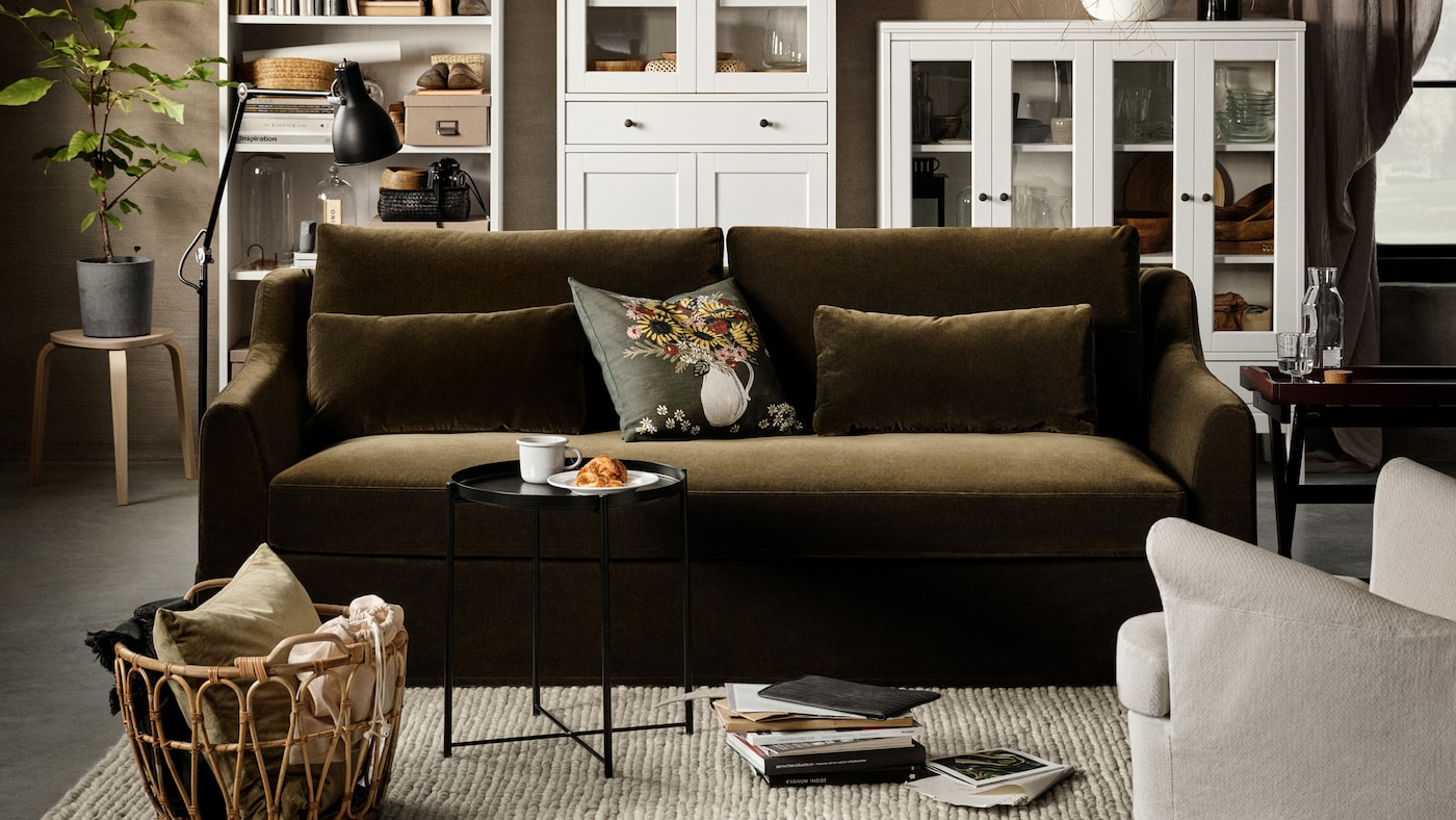 A dark olive-green 2-seat sofa, a white high cabinet with glass doors and 1 drawer, a white bookcase, a birch stool.