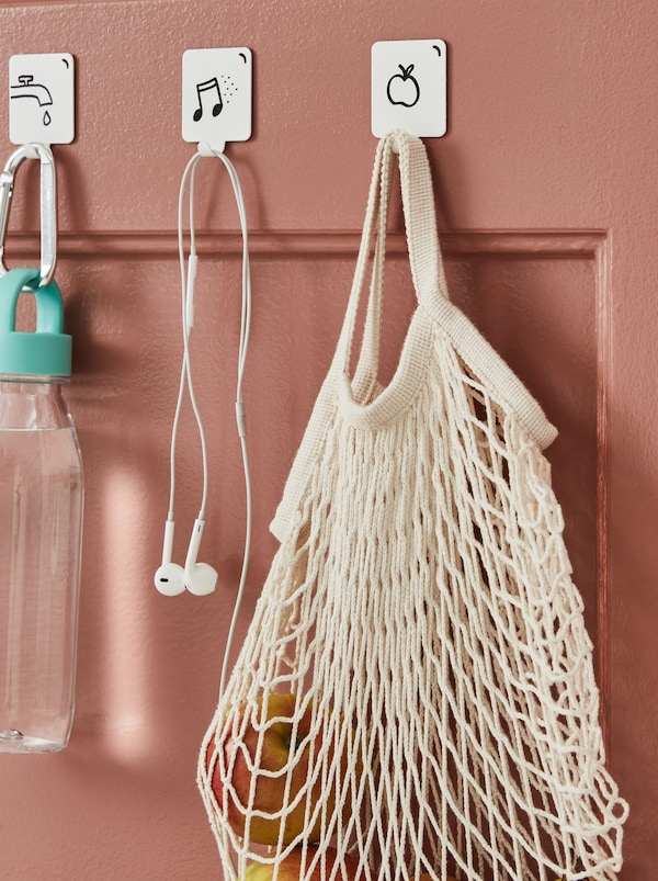 A dark-pink door fitted with graphic-motif hooks holding a water bottle, earphones and a KUNGSFORS net bag with fruit.