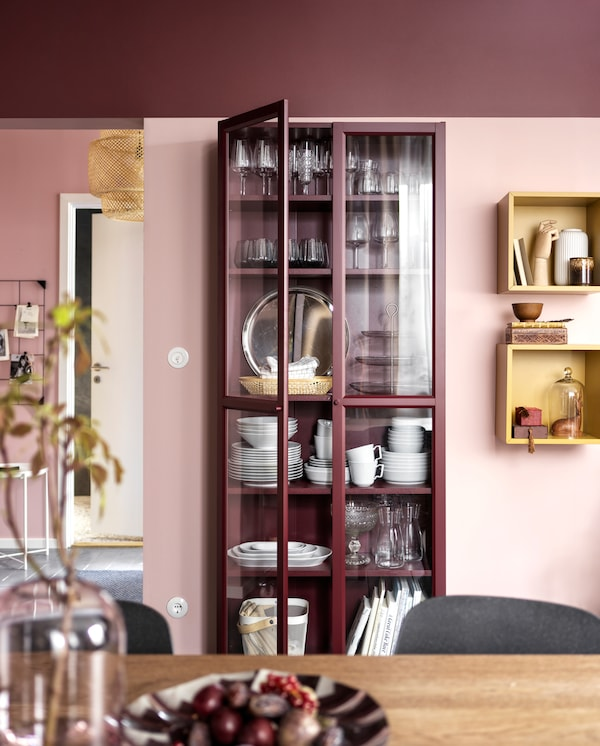 A dark red bookcase with glass-doors and stored dinnerware and two wall-mounted, golden-brown cubes with decorative items.