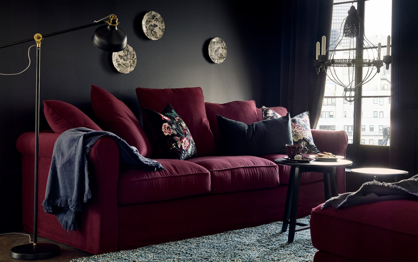 A dark red sofa with a blue throw blanket draped over it and floral accent cushions