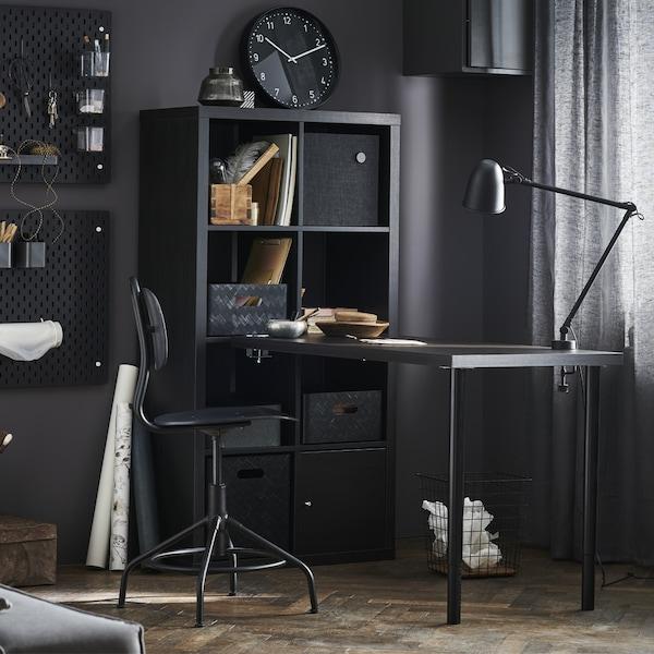 A dark room with black-brown KALLAX/LINNMON desk combination