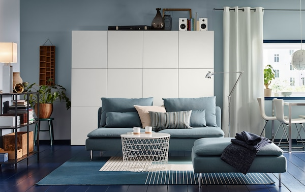 A dark walled living room furnished with IKEA SÖDERHAMN turquoise three-seater sofa and footstool.