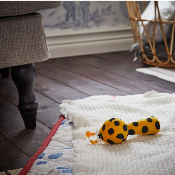 A dark wooden floor with a white/red/blue quilted blanket with a white blanket and a rattle in black and yellow on it.