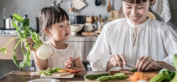 A daughter is cooking with her mother.