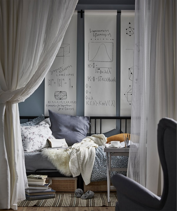 A day bed shown in a study zone with hanging curtains acting as a room divider.