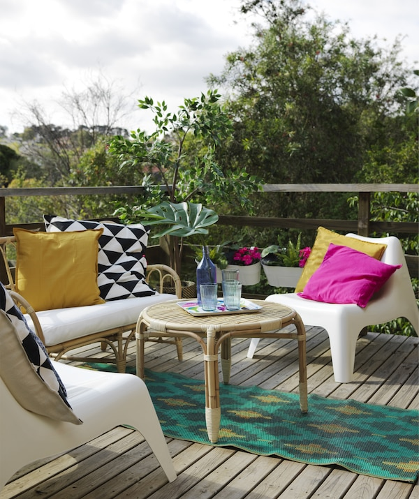 A deck area with MASTHOLMEN rattan sofa and table, plastic armchairs, a colourful rug and cushions.
