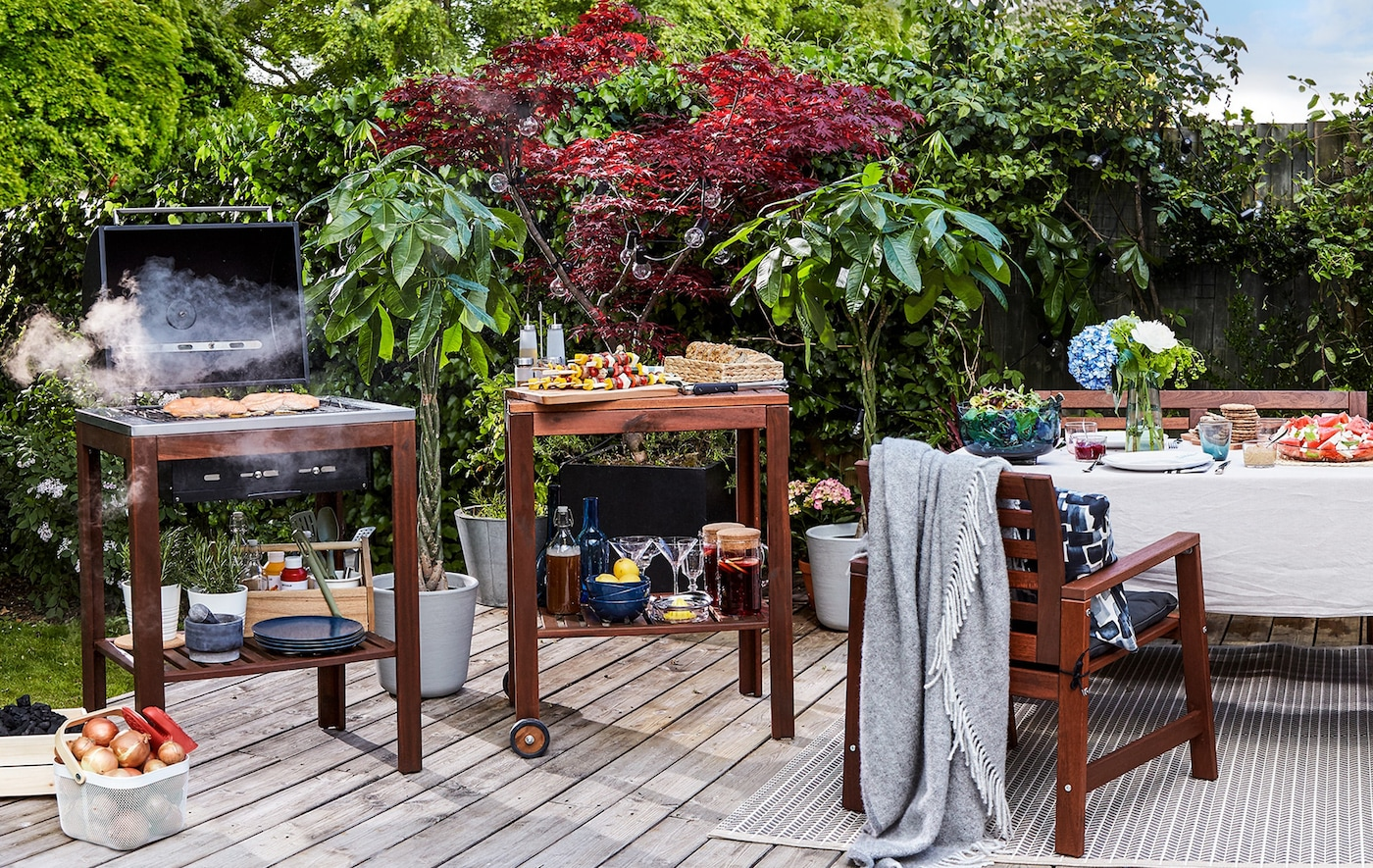 A decked area in a garden with dining table and chairs, food trolley and barbeque.
