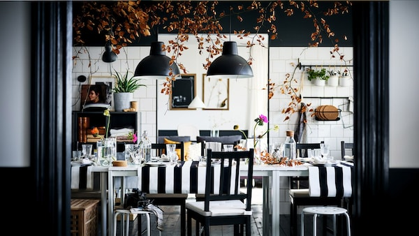 A decked-out black-and-white dining area with brown-black STEFAN chairs and MARIUS stools round two white MELLTORP tables.