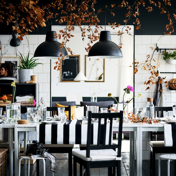 A decorated, black-and-white dining area with brown-black STEFAN chairs and MARIUS stools surrounding a white MELLTORP table.
