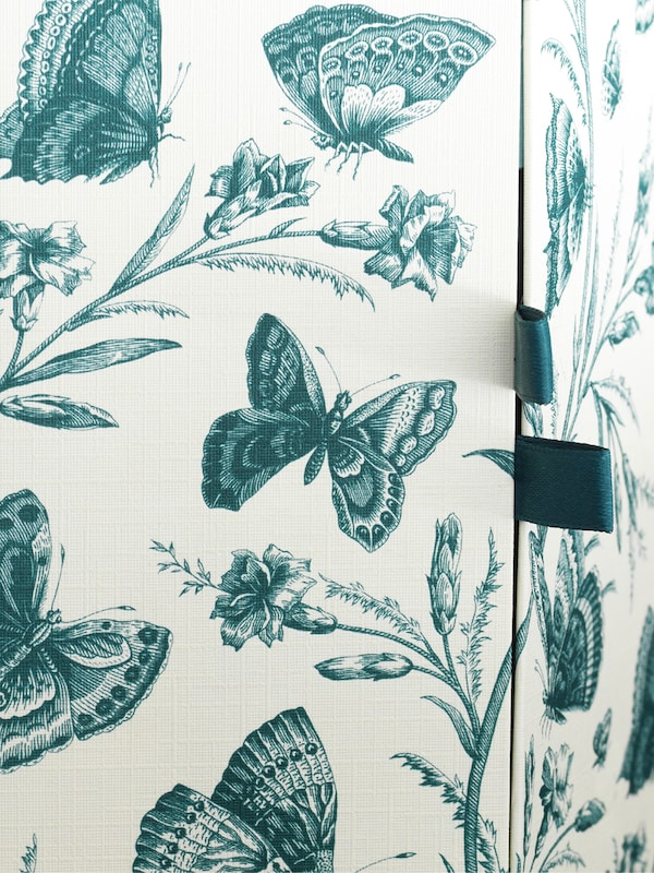 A decoration box with a bright design of assorted butterflies and flowering plant in greenish blue, two opening tabs.