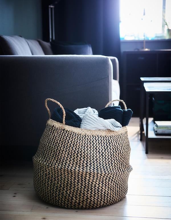 A decorative FLÅDIS basket storing living room textiles.